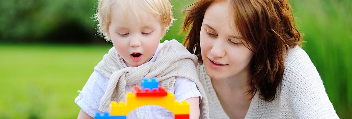 Au pair baut mit einem kleinen Jungen mit Legosteinen, Aupair Agentur Wagner, Hamm, Deutschland.