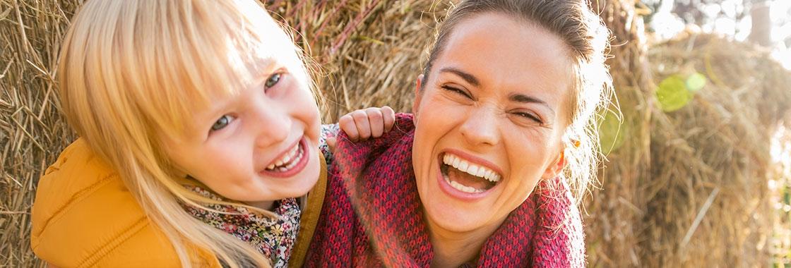 Au pair mit Mädchen spielt im Stroh, Aupair Agentur Wagner, Hamm, Deutschland.